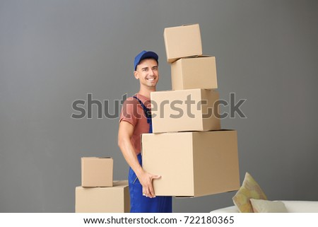 Delivery man holding boxes, indoors