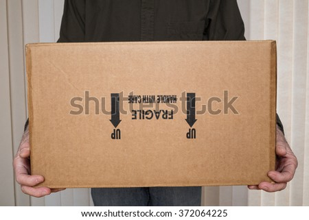 "Delivery man holding cardboard box marked ""fragile, handle with care"" upside down. - stock photo"