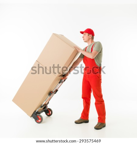 delivery man holding push cart loaded with cardboard boxes, on white background - stock photo