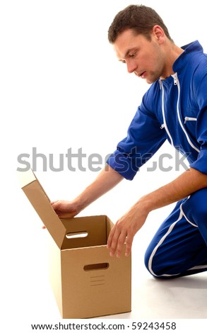 delivery man in blue coveralls with curiosity looks to carton box