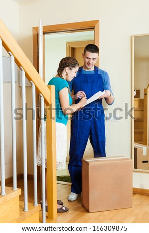 Delivery man in uniform delivered a parcel to woman at home - stock photo