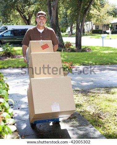Delivery man or mover pushing a dolly loaded with boxes up the front walk. - stock photo