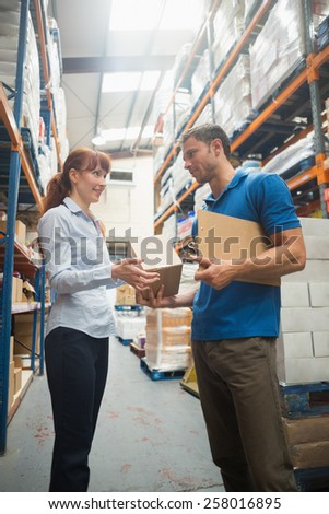 Delivery man passing parcel to warehouse manager in warehouse - stock photo