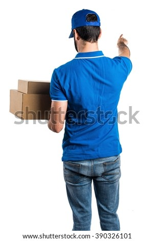 Delivery man pointing back - stock photo