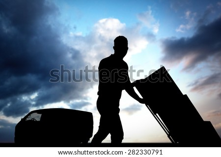 Delivery man pushing trolley of boxes against cloudy sky - stock photo