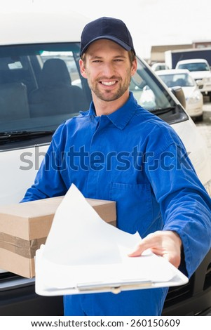 Delivery man showing clipboard to sign to customer outside the warehouse - stock photo