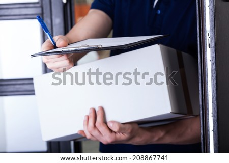 Delivery man supplying pack and asking for a signature - stock photo