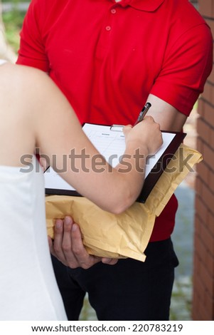 Delivery man with a package and woman signing documents - stock photo