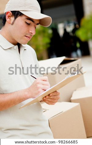 Delivery man with cardboard boxes taking notes - outdoors - stock photo