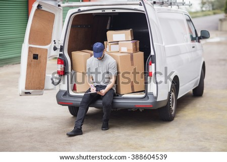 Delivery man writing on clipboard while sitting on the cargo area of his van - stock photo