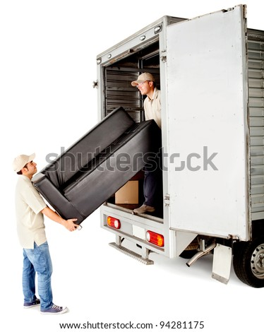 Delivery men with unloading a sofa from a truck - isolated over white - stock photo
