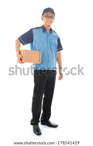 Delivery person delivering package smiling happy in blue uniform. Handsome Asian man courier full length isolated on white background. - stock photo