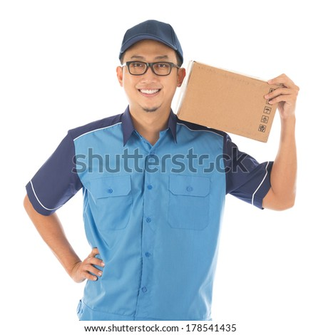 Delivery person delivering package smiling happy in blue uniform. Handsome young Asian man professional courier isolated on white background. - stock photo