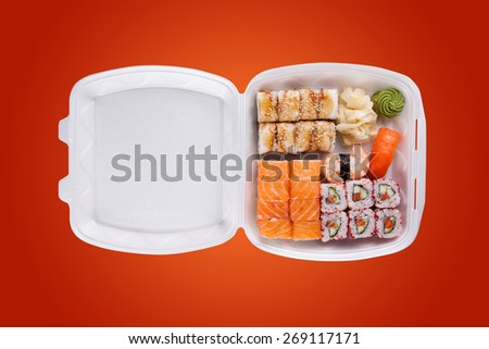 delivery service Japanese food rolls in plastic box on a orange background - stock photo
