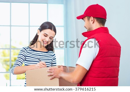 Delivery service worker in uniform delivering parcel to woman. Woman signing document on box - stock photo