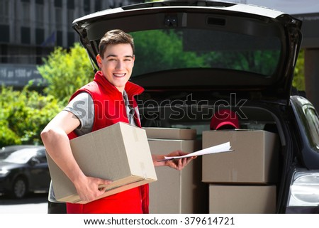 Delivery service worker in uniform delivering parcels and standing near car. Man holding box and document to sign, smiling and looking at camera - stock photo
