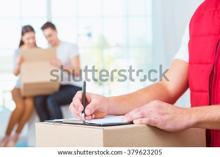 Delivery service worker in uniform delivering parcels to happy couple. Man with box signing document - stock photo