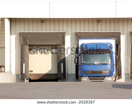 Delivery truck being unloaded in unloading dock area - stock photo