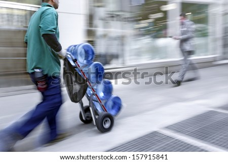 delivery water with dolly by hand, purposely motion blur - stock photo
