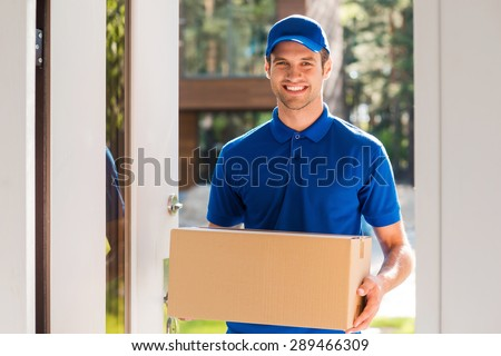 Delivery with smile. Cheerful young courier holding a cardboard box while standing at the entrance of apartment - stock photo