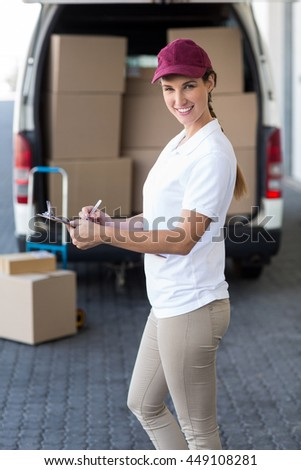 Delivery woman is holding a clipboard and smiling to the camera in front of her van