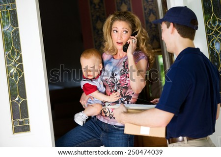 Delivery: Woman Very Busy As She Answers the Door - stock photo