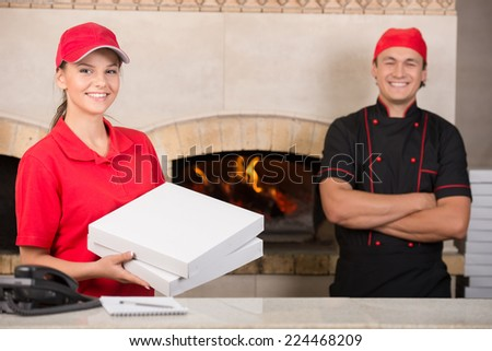 Delivery woman with boxes of pizza and chef. - stock photo