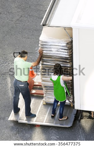 delivery workers  with hand pallet truck forklift equipment in street city - stock photo