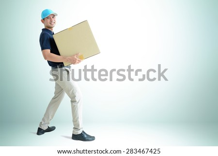 Deliveryman carrying a cardboard box on white gray background with copy space - stock photo