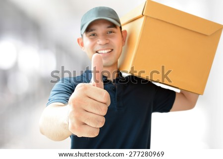 Deliveryman carrying a parcel box, giving thumbs up - stock photo