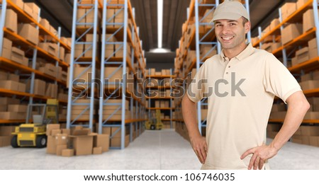 Deliveryman carrying a parcel in a distribution warehouse - stock photo