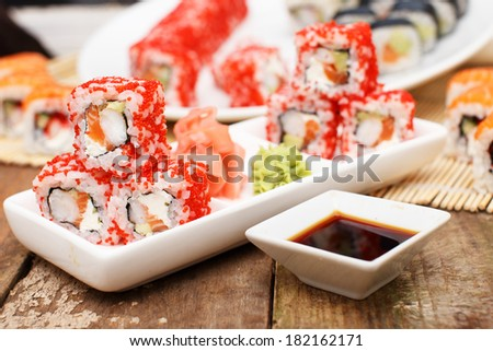 Deluxe sushi set with soy sauce on a wooden table - stock photo