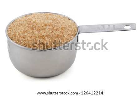 Demerara sugar presented in an American metal cup measure, isolated on a white background