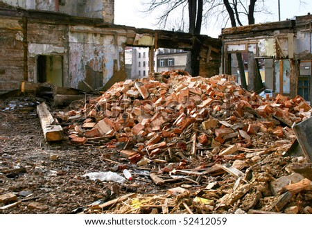 Demolished abandoned building with broken windows and wall in one of the street in center of Riga, Latvia. Bricks and many garbage of wooden boards in a front.