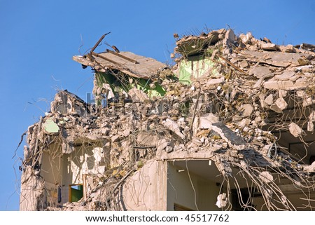 Demolished block of flats against blue sky - stock photo