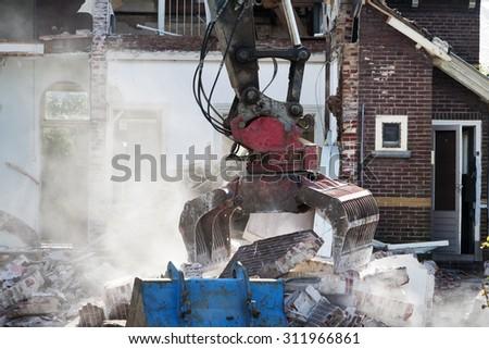 Demolishing an abandoned house with a grab - stock photo