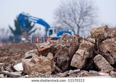 Demolishing site. Bricks of the demolished building on the foreground and defocused excavator on the background. - stock photo