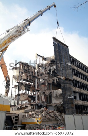 Demolition: building being demolished with rubble all around it. - stock photo