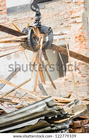 Demolition industry machine taking down walls of old factory building - stock photo