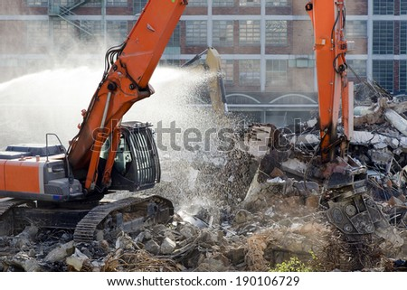 Demolition site of old factory building with heavy machines at work - stock photo