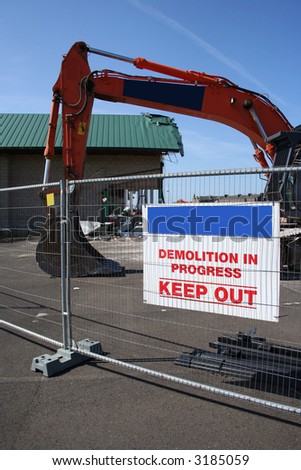 demolition site with heavy machinery and sign - stock photo