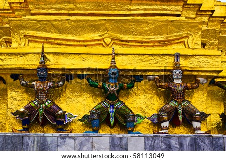 Demon Guardian Statues supporting golden Chedi at Wat Phra Kaew