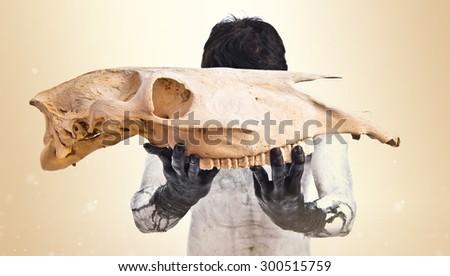 Demon holding horse skull over ocher background - stock photo
