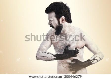Demon in pain over ocher background - stock photo