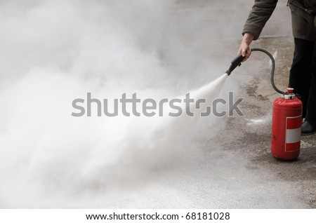 demonstrating how to use a fire extinguisher - stock photo