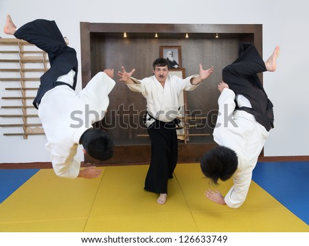 Demonstration Aikido with two partners. In  sports hall (dojo) - stock photo