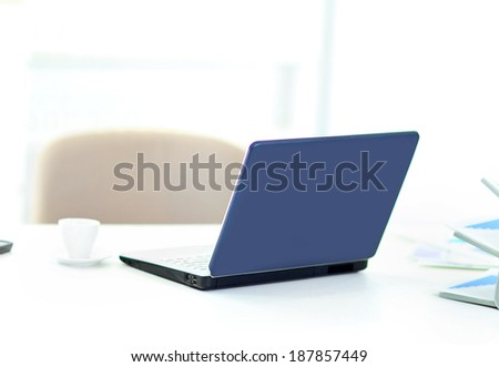 Demonstration of a laptop in the office of the rear view. - stock photo