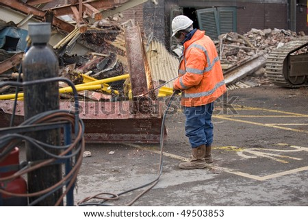 demotion worker using oxy acetylene burner on construction site