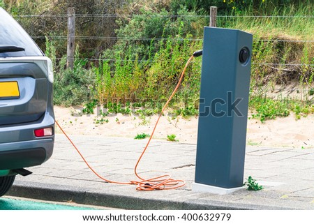 DEN HAAG, SCHEVENINGEN, THE NETHERLANDS - JUNE 17, 2015: Electric car at a charging station on the beach parking in Scheveningen Holland. Seperate parking with charging station for electric vehicles.