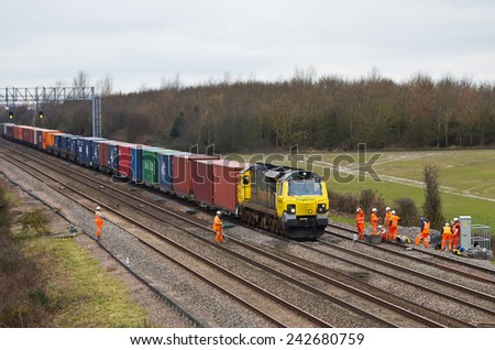 DENCHWORTH, UK - FEBRUARY 19: A freight train passes a team of Network Rail workers engaged in groundwork on the national infrastructure project to electrify the GWR on February 19, 2014 in Denchworth - stock photo